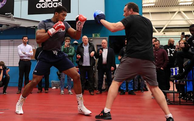 Anthony Joshua spars with trainer Robert McCracken (R)  - PA