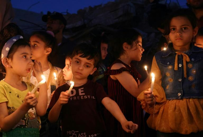 Palestinian children hold candles during a rally amid the ruins of houses destroyed by Israeli strikes in Gaza City on May 24