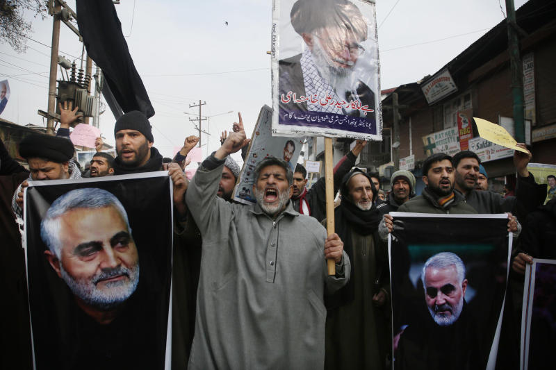 Kashmiri Shiite Muslims shout anti American and anti Israel slogans during a protest against U.S. airstrike in Iraq that killed Iranian Revolutionary Guard Gen. Qassem Soleimani, seen in the photographs, at Magam 37 kilometers (23 miles) north of Srinagar, Indian controlled Kashmir, Friday, Jan. 3, 2020. The killing of Iran's top military commander Gen. Qassem Soleimani triggered several anti-U.S. protests in Indian-controlled Kashmir, the protesters also shut down shops and businesses in Magam and Budgam towns in south Kashmir. (AP Photo/Mukhtar Khan)