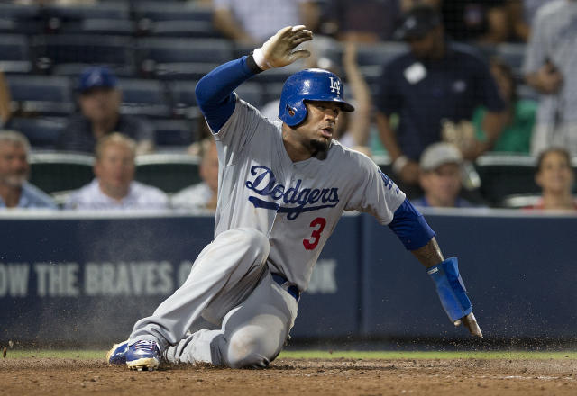 Los Angeles Dodgers' Carl Crawford (3) scores on a A.J. Ellis ground ball in the eighth inning of a baseball game against the Atlanta Braves Monday, Aug. 11, 2014 in Atlanta. (AP Photo/John Bazemore)