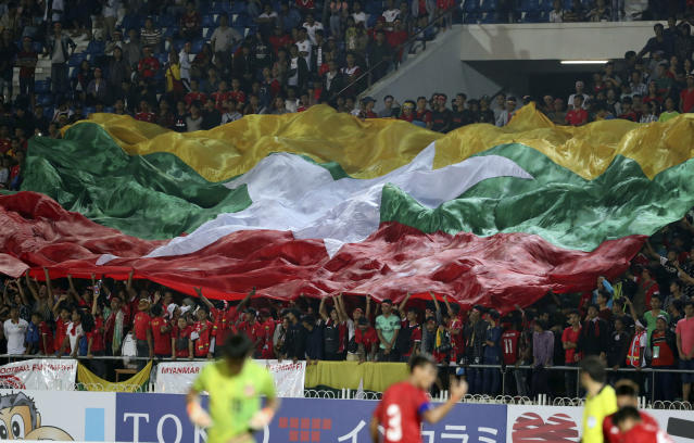 Myanmar fans wave the National Flag during the World Cup 2022 Group F qualifying soccer match between Myanmar and Japan at Thuwunna stadium Tuesday, Sept. 10, 2019, in Yangon, Myanmar. (AP Photo/Thein Zaw)