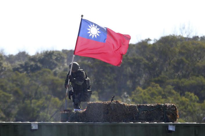 """FILE - In this Jan. 19, 2021, file photo, a soldier holds a Taiwanese flag during a military exercise aimed at repelling an attack from China in Hsinchu County, northern Taiwan. Japan believes rising tension surrounding Taiwan requires its attention """"with a sense of crisis"""" as China intensifies military activities in the area and the United States steps up support for the self-governing island. (AP Photo/Chiang Ying-ying, File)"""