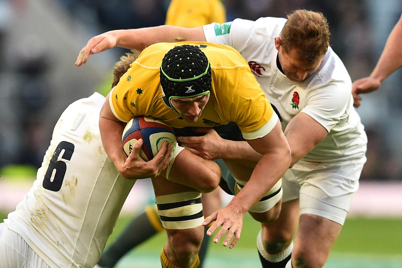 Australia's lock Rob Simmons (C) is tackled by England's flanker Chris Robshaw and England's hooker Dylan Hartley (R) during the international rugby union test match between England and Australia at Twickenham stadium in south-west London on December 3, 2016. (AFP Photo/Glyn KIRK)