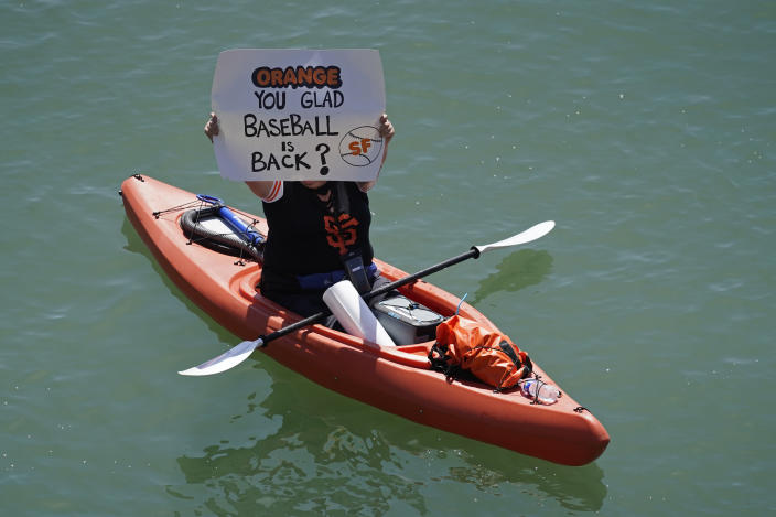 A woman kayaker holds up a sign in McCovey Cove before the start of an opening day baseball game between the San Francisco Giants and the Colorado Rockies, Friday, April 9, 2021, in San Francisco. (AP Photo/Eric Risberg)