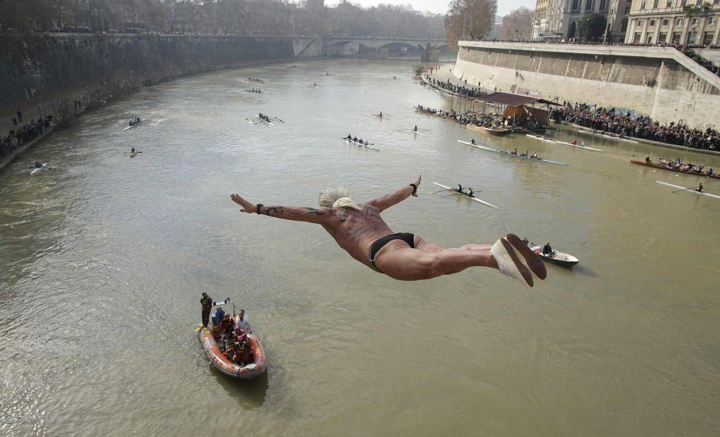 Maurizio Palmulli of Italy dives into the Tiber River from the Cavour bridge, as part of traditional New Year celebrations January 1, 2013. Four men dived the muddy waters of the Tiber from the Cavour bridge, continuing an annual tradition which dates back to 1946.