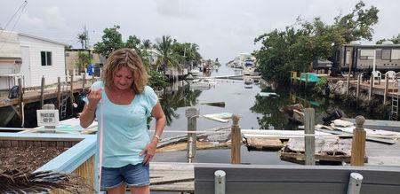 Terri Metter stands in front of what's left of destroyed trailers, that fill a canal near a trailer park in Marathon, Florida, U.S., June 10, 2018.  Picture taken June 10, 2018.  REUTERS/Zach Fagenson