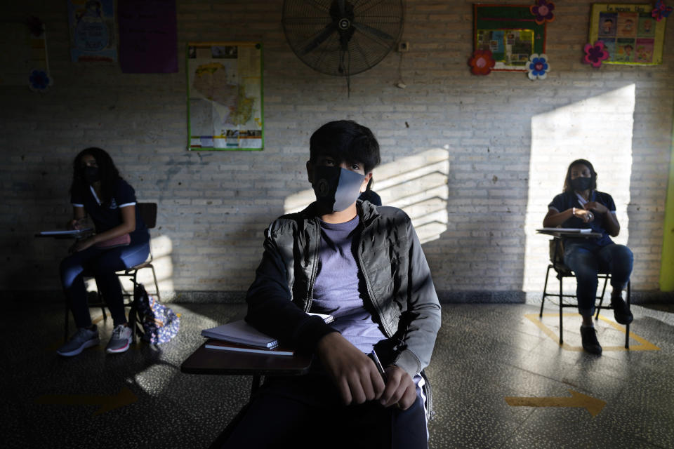 Eighth graders sit in a socially distanced classroom at the National School 1044 Santa Ana, on the first day that teachers are required to offer in-person instruction in Asuncion, Paraguay, Monday, Aug. 30, 2021. It had been one and a half years of remote learning due to the COVID-19 pandemic. (AP Photo/Jorge Saenz)