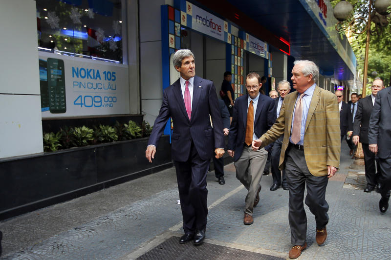 U.S. Secretary of State John Kerry, left, and his friend and fellow Vietnam War veteran Tommy Vallely, right, walk along a street in Ho Chi Minh City, Vietnaqm to attend a service at the Notre Dame Cathedral, Saturday, Dec. 14, 2013. Forty-four years after first setting foot in the country as a young naval officer, Kerry returned once more to Vietnam on Saturday, this time as America's top diplomat offering security assurances and seeking to promote democratic and economic reform. (AP Photo/Brian Snyder, Pool)