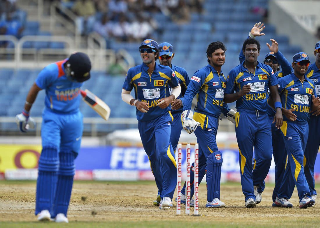 Sri Lankan cricket team captain Angelo Mathews (3rd L) celebrates with his teammates after dismissing India batsman Virat Kohli (L) during the third match of the Tri-Nation series between India and Sri Lanka at the Sabina Park stadium in Kingston on July 2, 2013. Sri Lanka have scored 348/1 at the end of their innings. AFP PHOTO/Jewel Samad