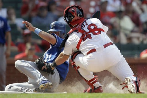 Kansas City Royals' Jeff Francoeur, left, is tagged out by St. Louis Cardinals catcher Tony Cruz while trying to score during the 11th inning of a baseball game on Sunday, June 17, 2012, in St. Louis. (AP Photo/Jeff Roberson)