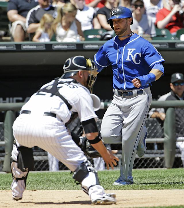 Kansas City Royals' Alex Gordon, right, scores as Chicago White Sox catcher Tyler Flowers fields the late throw during the fourth inning of a baseball game in Chicago on Saturday, June 14, 2014. (AP Photo/Nam Y. Huh)