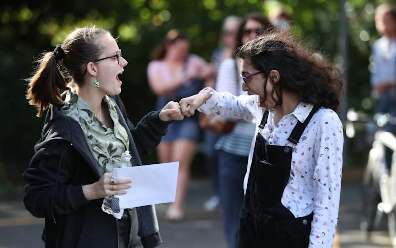 Two students congratulate each other after receiving their A level results last year - Andrew Matthews/PA