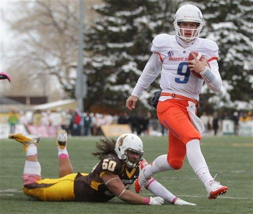 Boise State quarterback Grant Hedrick runs for a touchdown past Wyoming defender Mike Purcell during the third quarter of an NCAA college football game Saturday, Oct. 27, 2012, in Laramie, Wyo. Boise State won 45-14. (AP Photo/Michael Smith)