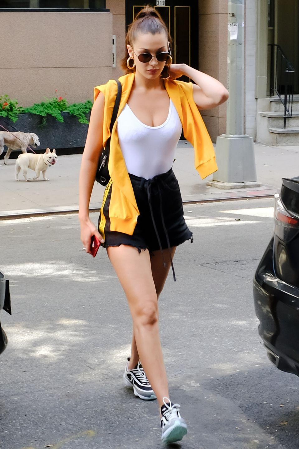 <p>In a white tank top, yellow draped sweatshirt, Off-White cutoff shorts, Nike trainers, rounded sunglasses, gold hoop earrings and a black bag while out in New York.</p>
