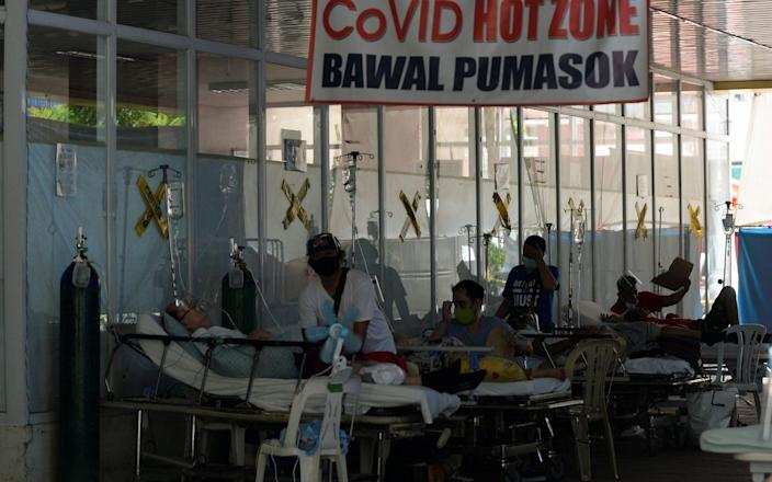 Suspected coronavirus patients lie on hospital beds outside the emergency room of Amang Rodriguez Memorial Medical Center, in Marikina City, Metro Manila - Reuters