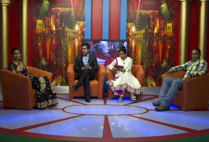 """In this July 26, 2013 photo, Nidhi Gaur, far left and her fiance Rahul Rai, far right, participate in """"So It's Final,"""" a talk show on Shagun TV that features engaged couples in Noida, India. Indians are obsessed with weddings and obsessed with reality television. Now Shagun TV, a new television channel headquartered in a sprawling suburb of India's capital, is hoping it has found a can't-miss idea — merging the two into a 24-hour matrimonial TV station.(AP Photo/Tsering Topgyal)"""