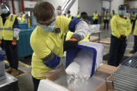 FILE - In this Dec. 13, 2020, file photo, dry ice is poured into a box containing the Pfizer COVID-19 vaccine as it is prepared to be shipped at the Pfizer Global Supply Kalamazoo manufacturing plant in Portage, Mich. As millions continue to wait their turn for the COVID-19 vaccine, small but steady amounts of the precious doses have gone to waste across the country. By one World Health Organization estimate, more than half of all vaccines in previous campaigns worldwide have been thrown away because they were mishandled, unclaimed or expired. (AP Photo/Morry Gash, Pool, File)