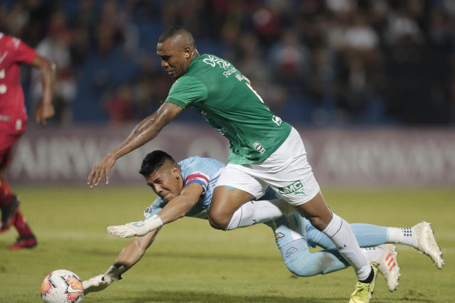 Angelo Rodriguez of Colombia's Deportivo Cali fight for the ball with goalkeeper Pablo Gavilan of Paraguay's River Plateduring a Copa Sudamericana soccer game in Asuncion, Paraguay, Tuesday, Feb. 25, 2020. (AP Photo/Jorge Saenz)