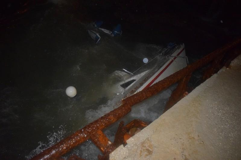 A sailing boat where two people were found dead is seen half submerged in the water after a storm, next to a pier in Antirio