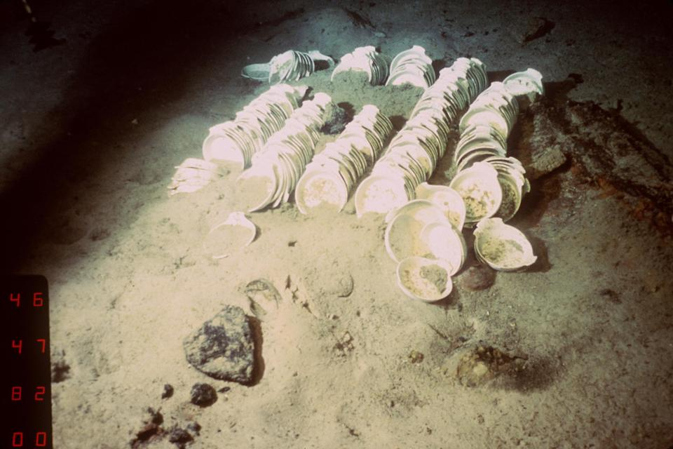 A dimly lit shot of stacks of dishes on the ocean floor