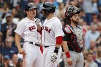 Boston Red Sox's J.D. Martinez, center, celebrates his two-run home run that also drove in Hunter Renfroe, left, as Cleveland Indians' Austin Hedges, right, looks on during the sixth inning of a baseball game, Sunday, Sept. 5, 2021, in Boston. (AP Photo/Michael Dwyer)