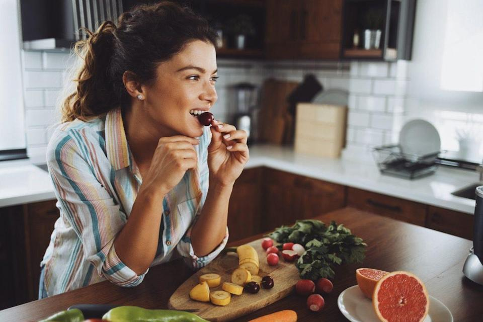 A young smiling woman having healthy breakfast in the morning