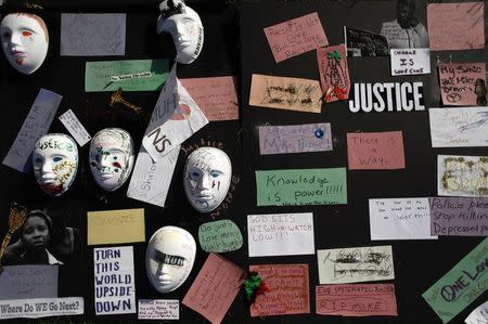 Messages written on papers and masks are displayed on a board along Canfield Drive where Michael Brown was fatally shot by a police officer in Ferguson, Missouri, August 24, 2014. REUTERS/Joshua Lott