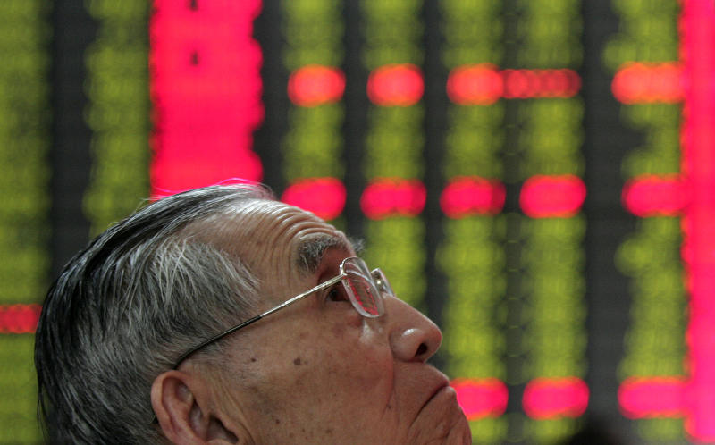 An investor looks at the stock price monitor at a private securities company Tuesday April 10, 2012 in Shanghai, China. Asian stocks were mostly lower Tuesday as a four-day slump in U.S. markets sparked by concern about the strength of the world's biggest economy weighed on investor confidence. (AP Photo)