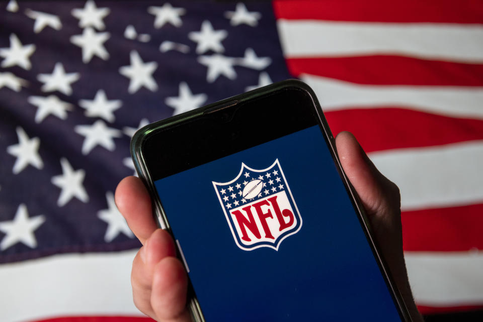 Football and your phone, made in America. (Photo Illustration by Budrul Chukrut/SOPA Images/LightRocket via Getty Images)