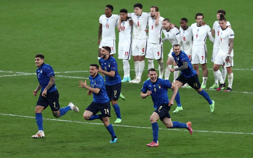 Players of Italy celebrate following victory in the penalty shoot out as players of England look dejected during the UEFA Euro 2020 final - Getty Images
