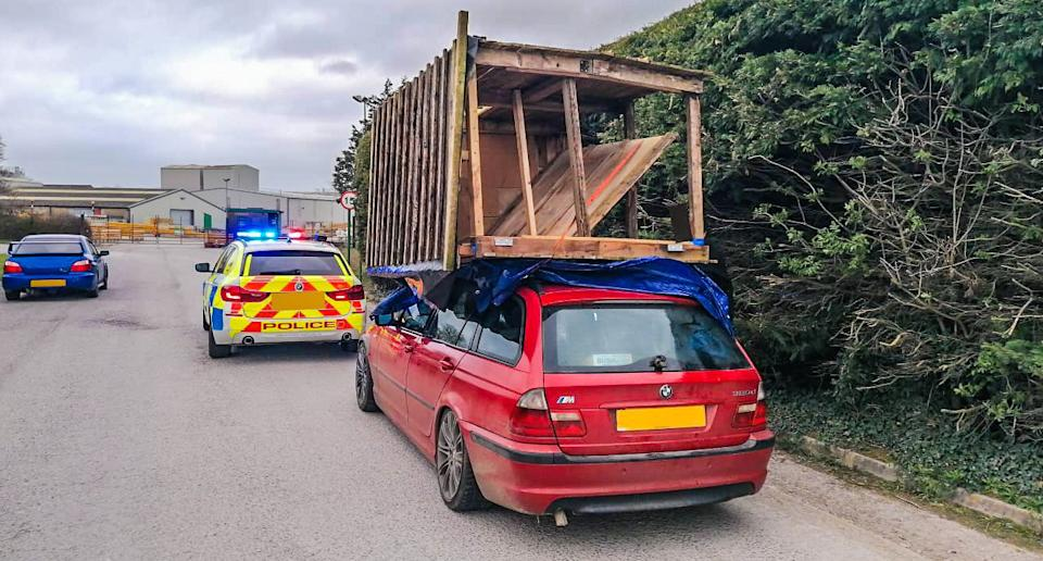 A BMW with a shed strapped to the roof is pictured.