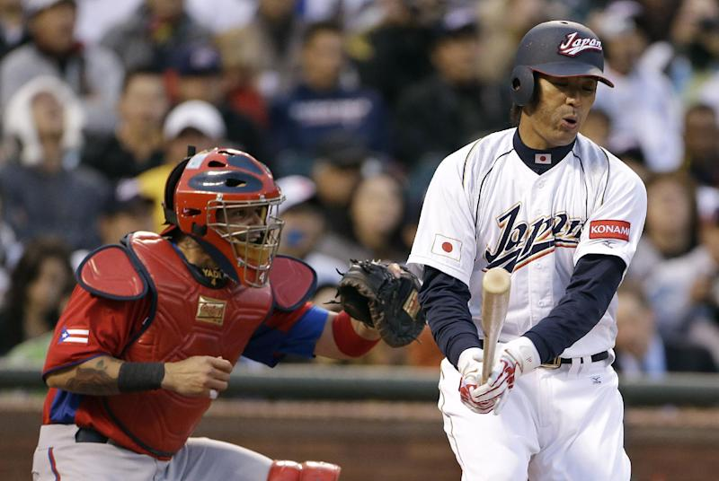 Japan's Atsunori Inaba, right, reacts after striking out against Puerto Rico's Mario Santiago during the third inning of a semifinal game of the World Baseball Classic in San Francisco, Sunday, March 17, 2013. At left is catcher Yadier Molina. (AP Photo/Eric Risberg)