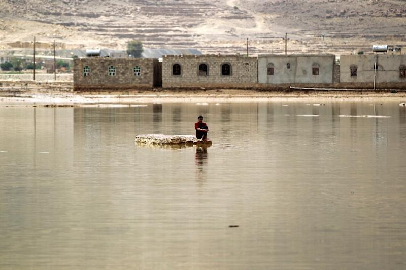 A man sits on a rock in a flooded street following heavy rain in the city of Amran, 50 kms north of Yemen's capital Sanaa on April 15, 2016