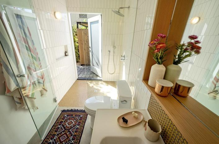 The bathroom door of the ADU opens out to the yard.