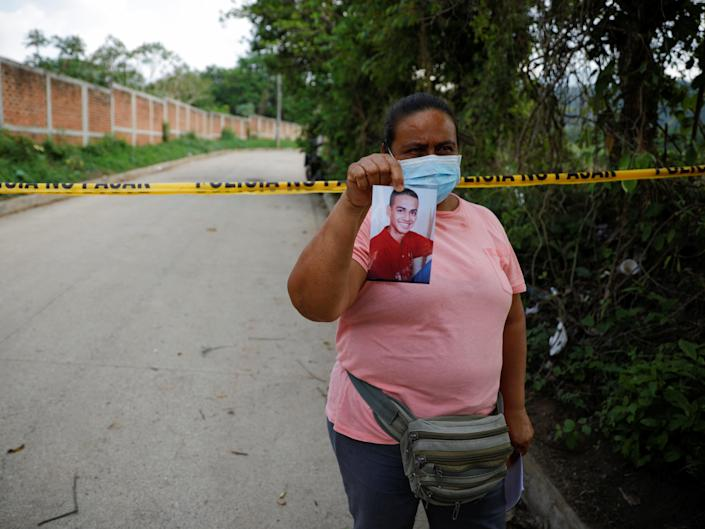 Marleny Barrientos shows a picture of her son who went missing six years ago and is believed to be at the site authorities are excavating. (REUTERS)