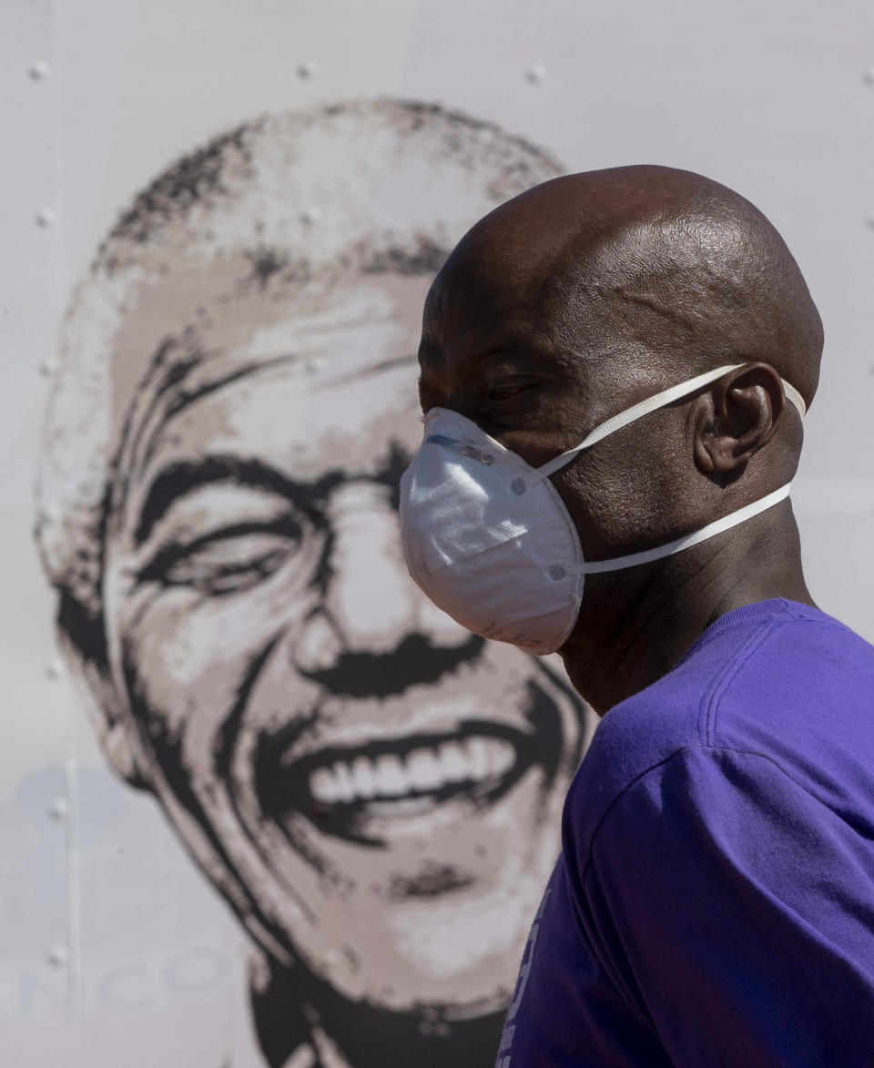 A man wearing a face mask walks past a portrait of former South African president Nelson Mandela on a mobile clinic at Lenasia South, south Johannesburg, South Africa, Tuesday, April 21, 2020, during a campaign aimed to combat the spread of the COVID-19 Coronavirus. (AP Photo/Themba Hadebe)