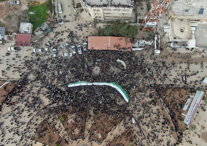 People carry opposition flags during a demonstration, marking the 10th anniversary of the start of the Syrian conflict, in the opposition-held Idlib, Syria