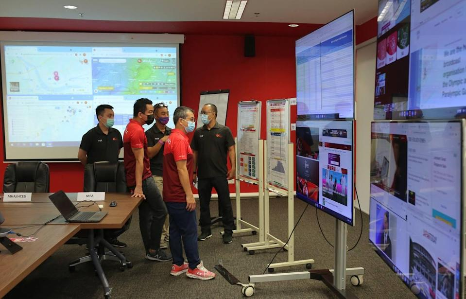Minister for Culture, Community and Youth Edwin Tong (centre, red shirt) at the Crisis Ops Centre set up for Team Singapore athletes going to the Tokyo Olympics. (PHOTO: Facebook/Edwin Tong)