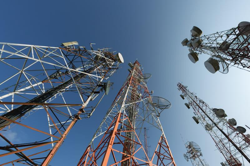 A cluster of cell towers viewed from below.