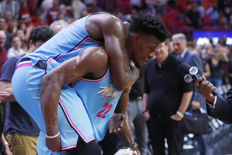 Miami Heat center Bam Adebayo jumps onto the back of forward Jimmy Butler as Butler is interviewed after the team's NBA basketball game against the Indiana Pacers, Friday, Dec. 27, 2019, in Miami. The Heat won 113-112. (AP Photo/Wilfredo Lee)