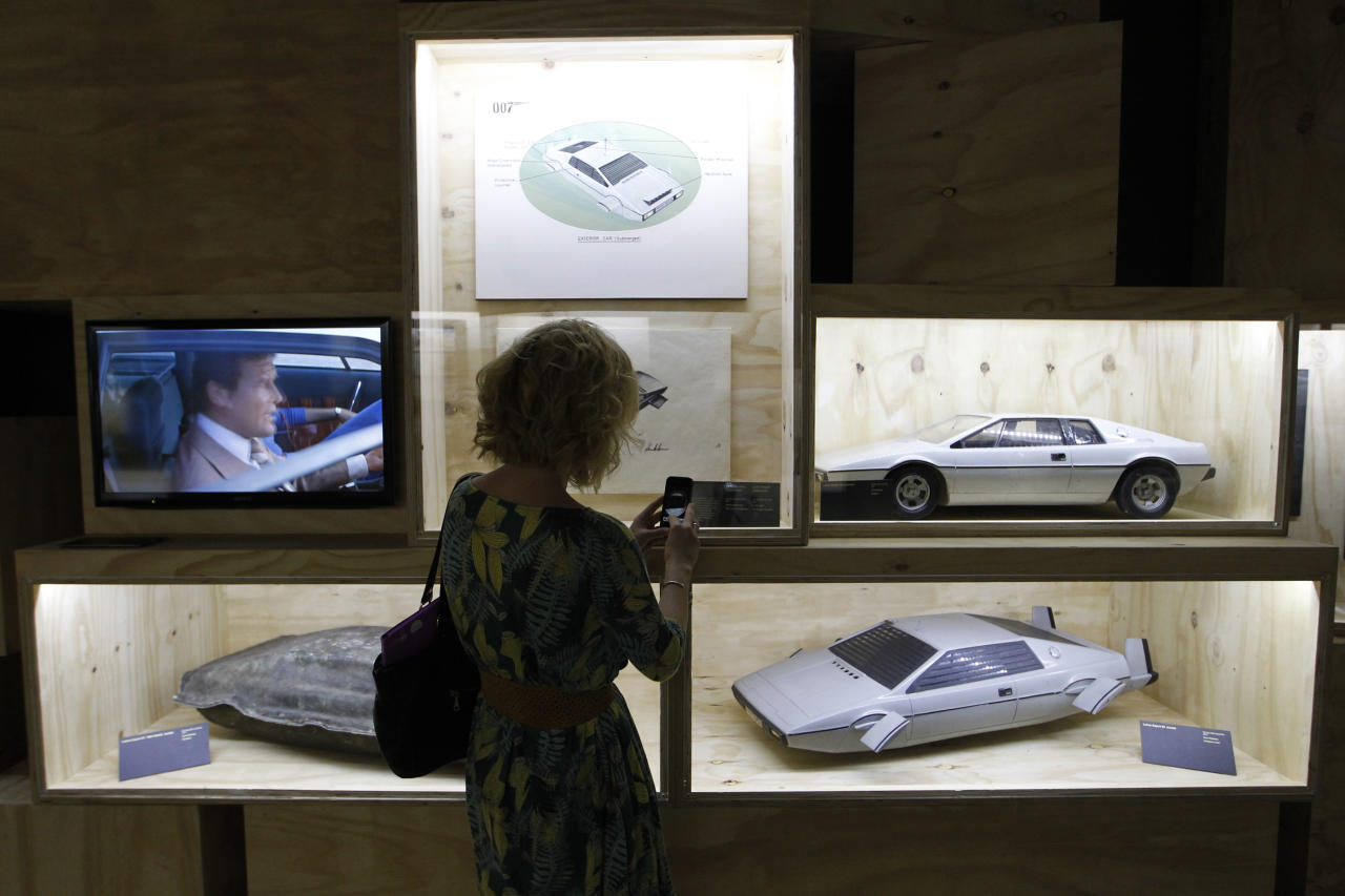 A visitor takes picture of models of James Bond's Lotus Esprit used in the film 'The Spy Who Loved Me' on display in the exhibition 'Designing 007 - Fifty Years of Bond Style' at the Barbican centre in London, Thursday, July 5, 2012. (AP Photo/Sang Tan)