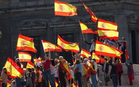 People wave Spanish flags during a mass protest by people angry with Catalonia's declaration of independence - Credit: AP Photo/Paul White