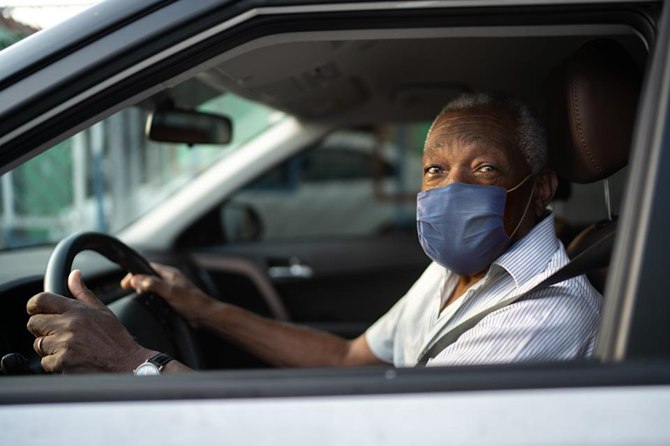 Portrait of senior african man driving a car with face mask