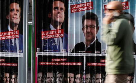 A man walks past campaign posters of candidates Jean-Luc Melenchon of the Parti de Gauche and Emmanuel Macron head of the political movement En Marche! (Onwards!) who run in the 2017 French presidential election in Paris
