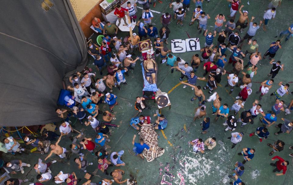 Inmates gather around the corpses of two inmates during a prison riot in Miguel Castro Castro prison, in Lima, Peru, Monday, April 27, 2020. Peru's prison agency reported that several prisoners died from causes still under investigation after a riot at the prison. Inmates complain authorities are not doing enough to prevent the spread of coronavirus inside the prison. (AP Photo/Rodrigo Abd)
