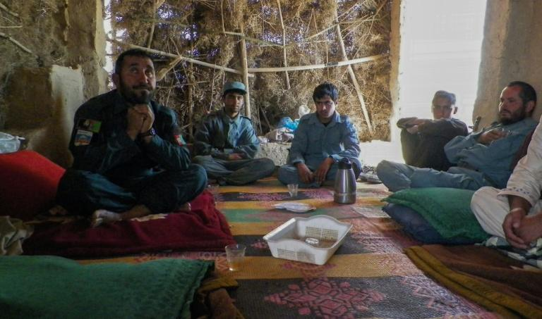 Afghan police commander Seddiqullah, 30, (L) sits with his subordinates as he speaks to AFP about the use of child sex slaves by the Taliban to attack police in Tarin Kot, Uruzgan