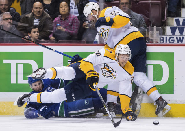 Nashville Predators' Miikka Salomaki, front, of Finland, falls over Vancouver Canucks' Troy Stecher, left, who was tripped by Nashville's Austin Watson (51) during the first period of an NHL hockey game Thursday, Dec. 6, 2018, in Vancouver, British Columbia. (Darry Dyck/The Canadian Press via AP)