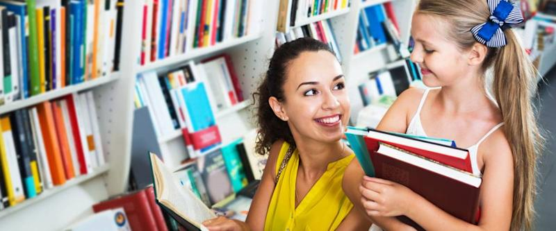 Portrait of smiling young mother with daughter reading textbook in book shop