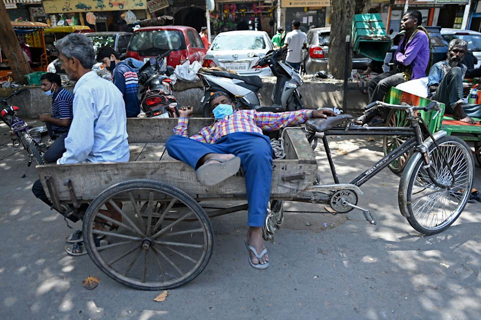 Rickshaw drivers rest along a street in the old quarters of New Delhi on April 19, 2021, as India's capital will impose a week-long lockdown from tonight, officials said, while the megacity struggles to contain a huge surge in Covid-19 cases with hospitals running out of beds and oxygen supplies low. (Photo by Sajjad HUSSAIN / AFP) (Photo by SAJJAD HUSSAIN/AFP via Getty Images)