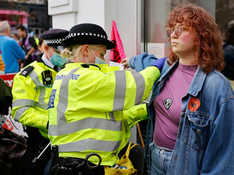 A climate activist from XR is searched by police officers before being arrested (AFP via Getty Images)